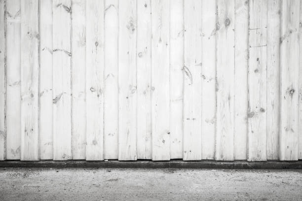 white wooden wall and asphalt pavement